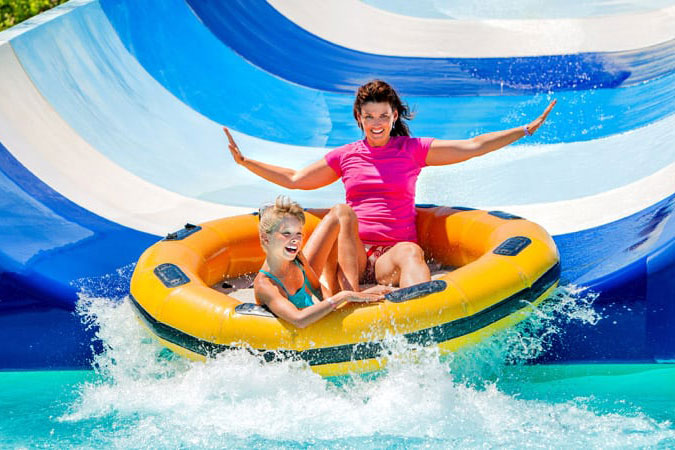 mother and daughter riding down a water slide in a tube